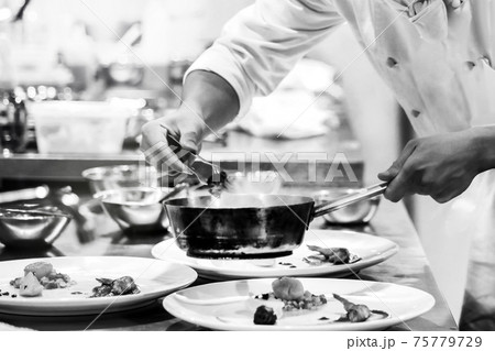 Chef cooking in a kitchen, chef at work, Black and White. 75779729