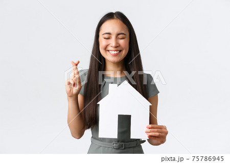 Insurance, loan, real estate and family concept. Hopeful smiling asian woman praying finding new apartment, cross fingers good luck, making wish with closed eyes, holding paper house 75786945