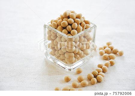 ガラスの器に入った大豆と散らばった大豆 75792006
