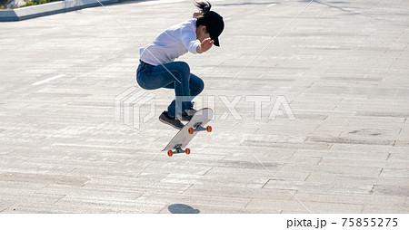 Asian woman skateboarder skateboarding in modern city 75855275