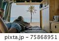 The girl is in the van watching the ocean 75868951