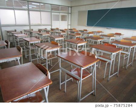 学校の教室の中にある机と椅子と黒板 75875284