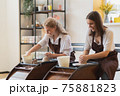 Two girls working on potters wheel making clay handmade craft in pottery workshop, friendship and guidance concept 75881823