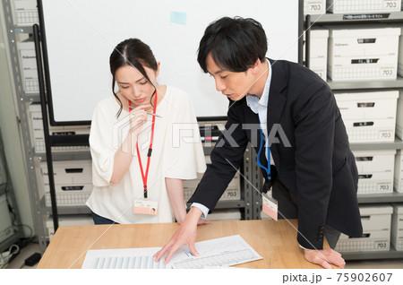 書類を見ながら女性社員にアドバイスする上司 75902607
