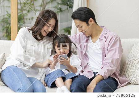 スマートフォンを持った女の子と両親 若い家族イメージ 75905128