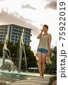 夕方のプールサイドを歩くハーフの女性 75922019