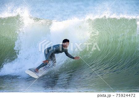 湘南の海でサーフィンをする男性 75924472