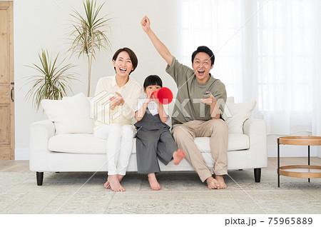 テレビでスポーツ観戦する親子3人のファミリー 75965889