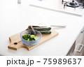 木のまな板に乗ったナスときゅうりの糠漬けとガラスの器に入った漬物②キッチンと包丁 75989637