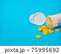Yellow pills and plastic white bottle 75995692