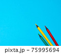Green, Yellow and Red Pencils on Blue Background 75995694