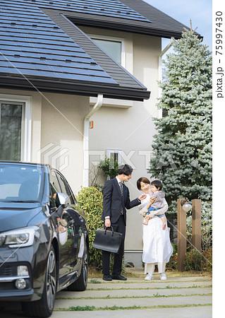 出勤する夫を見送り妻と赤ちゃん 75997430