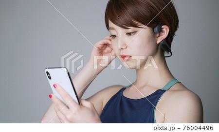 スマホで音楽を聴く女性 76004496