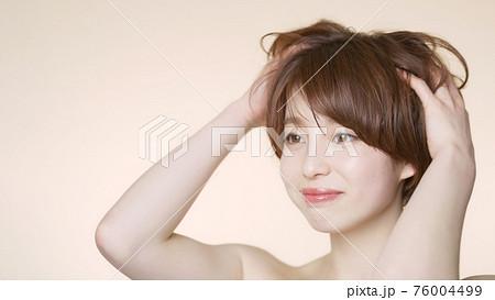 髪をくしゃくしゃにするショートヘアの女性 ヘアケアイメージ  76004499