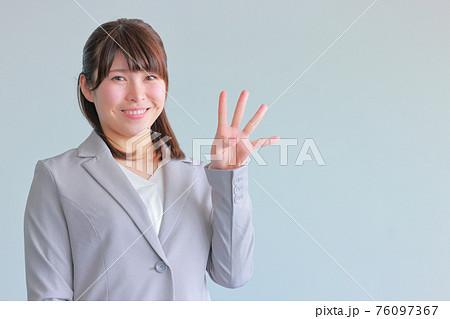 4つ目のポイントのポーズ_笑顔のスーツ女性 76097367