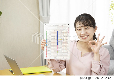 確定申告書類を持って微笑む女性 76121232