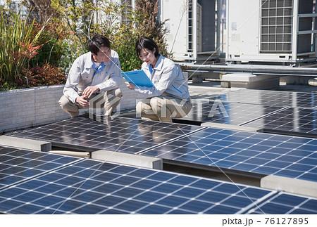 ソーラーパネルの点検をする作業員 76127895
