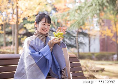 秋の公園でブドウを持つ女性(笑顔) 76130997