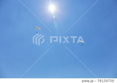 夏、空を飛ぶパラグライダー 76150750