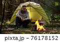 A man near a fire in the forest 76178152