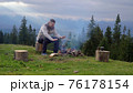 A man near a fire in the mountains 76178154