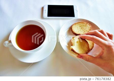 白い背景の紅茶とラスクとスマートフォン 右手持ち 76178382