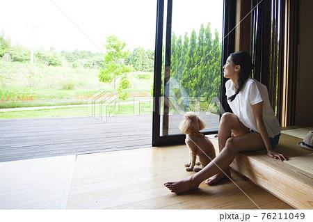 犬とコテージでくつろぐ女性 76211049