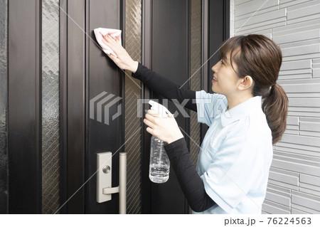 玄関のドアの拭き掃除をするハウスクリーニング の女性 76224563