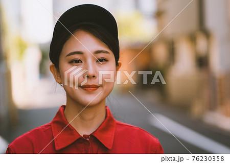 赤いつなぎを着た若い女性 76230358