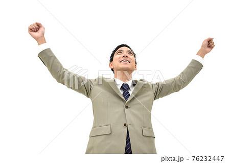 両手を上げて喜んでいるスーツの男性 白背景 76232447