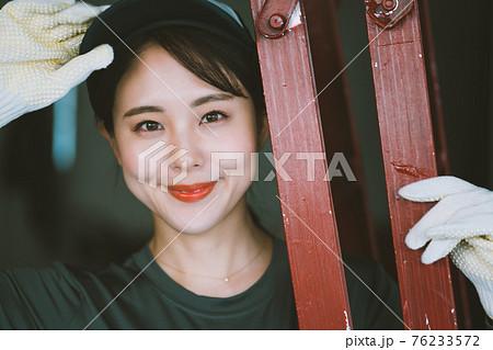 赤いつなぎを着た若い女性 76233572