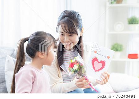 ファミリー 母の日に花束と手作りカードを渡す女の子とママ 76240491