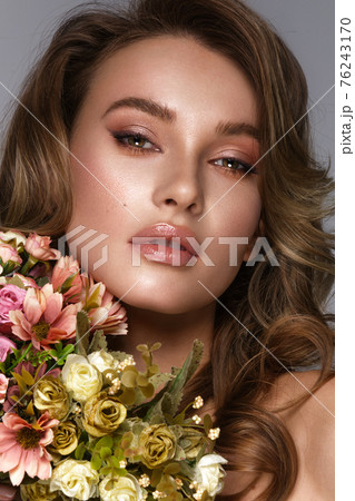 Beautiful woman with classic nude make-up, light hairstyle and flowers. Beauty face. 76243170