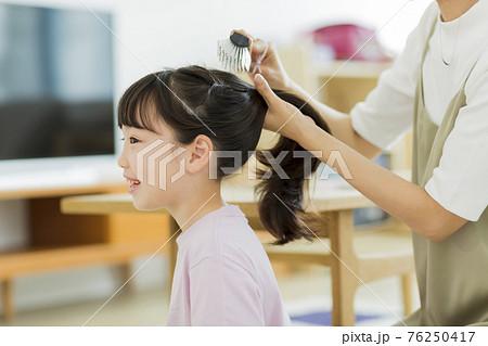 母親に髪をブラッシングしてもらう女の子  76250417