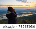 Rear view of female photographer photographing the view of Mekong river on mountain in morning 76265930
