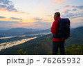 Senior man enjoys the view of cliff after hiked the hill to watch the sunrise over mekong river in morning at phu pha dak in nong khai, Thailand 76265932