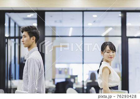 オフィスで背中合わせに立つ男女 ビジネスシーン 76293428