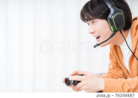 部屋でネットゲーム(オンラインゲーム)をプレイする男性 76299887