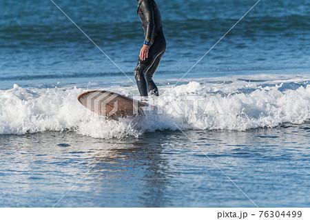 【強風吹き荒れる春の嵐の中のサーフィン】 76304499