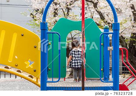 春の桜の咲く公園の遊具で遊ぶ女の子 76323728