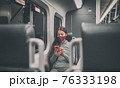 Train passenger using mobile phone during travel commute wearing face mask for coronavirus pandemic. Panoramic banner of people lifestyle commuting after work at night. 76333198