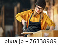 Joiner craftswoman working with wooden detail in workshop 76338989