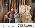 Happy couple of woodworkers standing near wooden plank 76338991