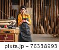 Female joiner using smartphone in workshop 76338993