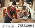 Cheerful joinery owners discussing project on laptop 76338994