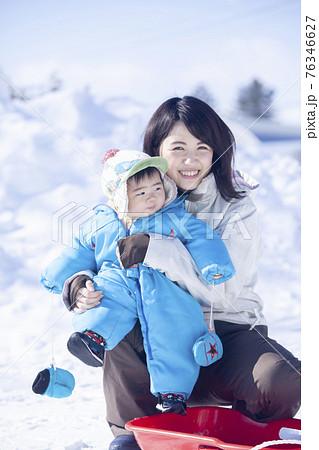 雪遊びを楽しむ、赤ちゃんとお母さん 76346627