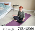 Girl meditate at home in bedroom near bed. Online 76348569