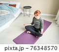 Girl meditate cross-legged at home in bedroom near 76348570