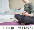Girl meditate cross-legged in bedroom. Bed and 76348571