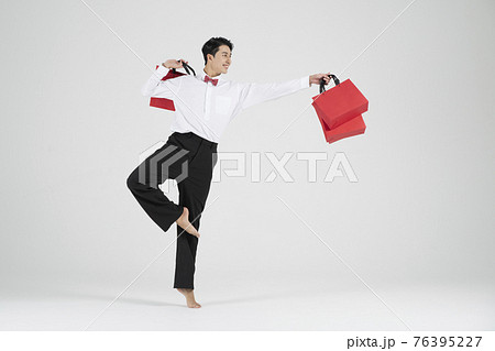 sale promotion concept, contemporary male dancer with shopping bags 76395227